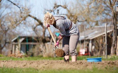 женщина копает в огороде