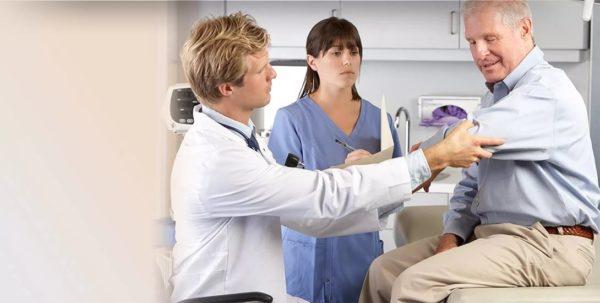 врач осматривает плечо